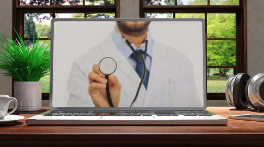 Laptop With Telemedicine Doctor Screen On Wooden Desk At Home. B
